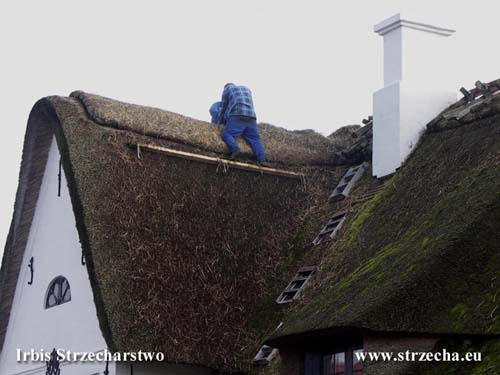 Service of thatched roofs - filling the straw ridge with new material